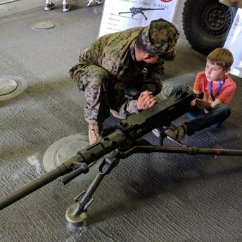 Kid learning to shoot a big gun